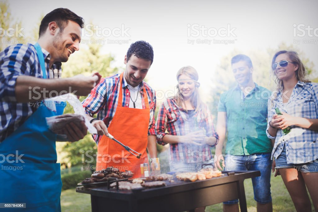 Happy friends grilling meat and enjoying barbecue party outdoors stock photo