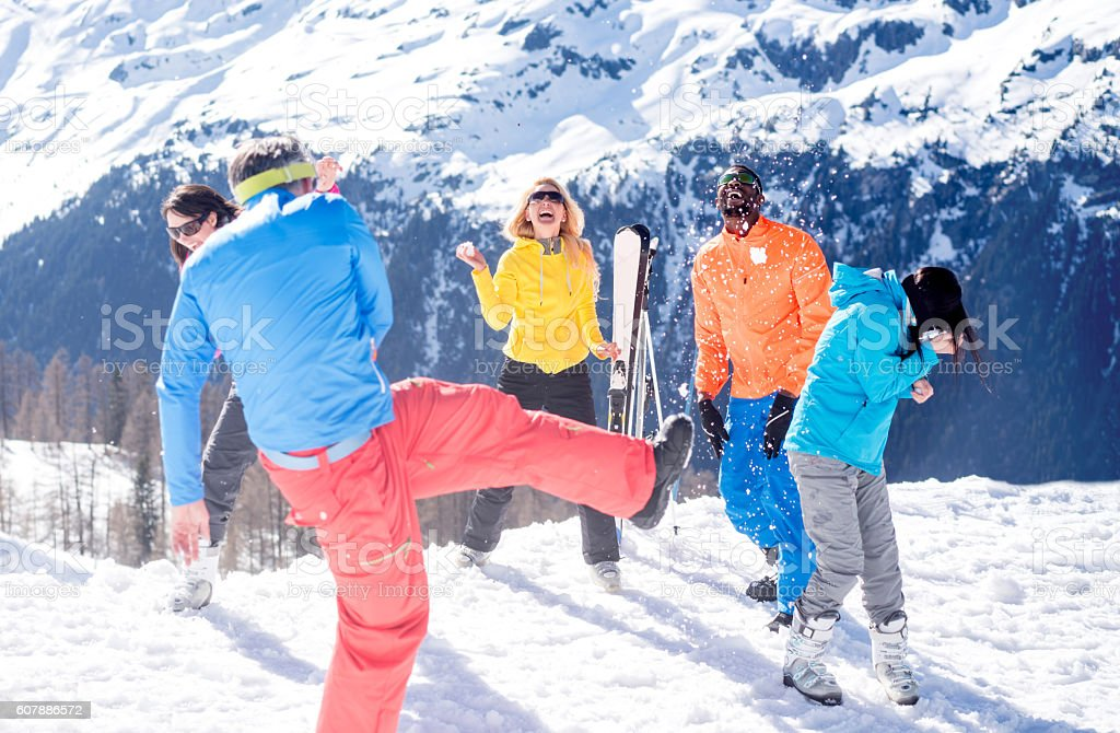 Happy friends having a snow fight stock photo