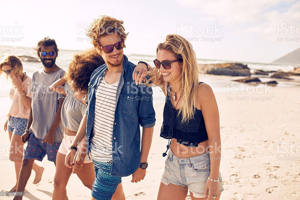 Happy friends having a walk on the beach stock photo