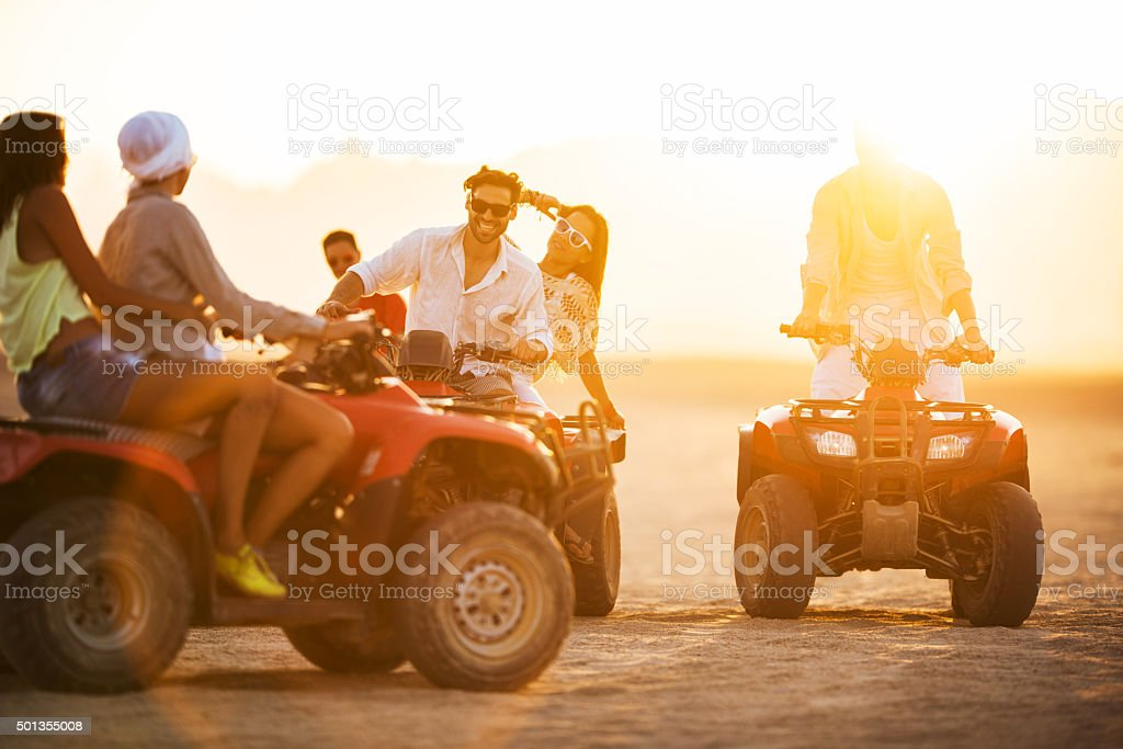 Happy friends having fun on quad bikes at sunset. stock photo