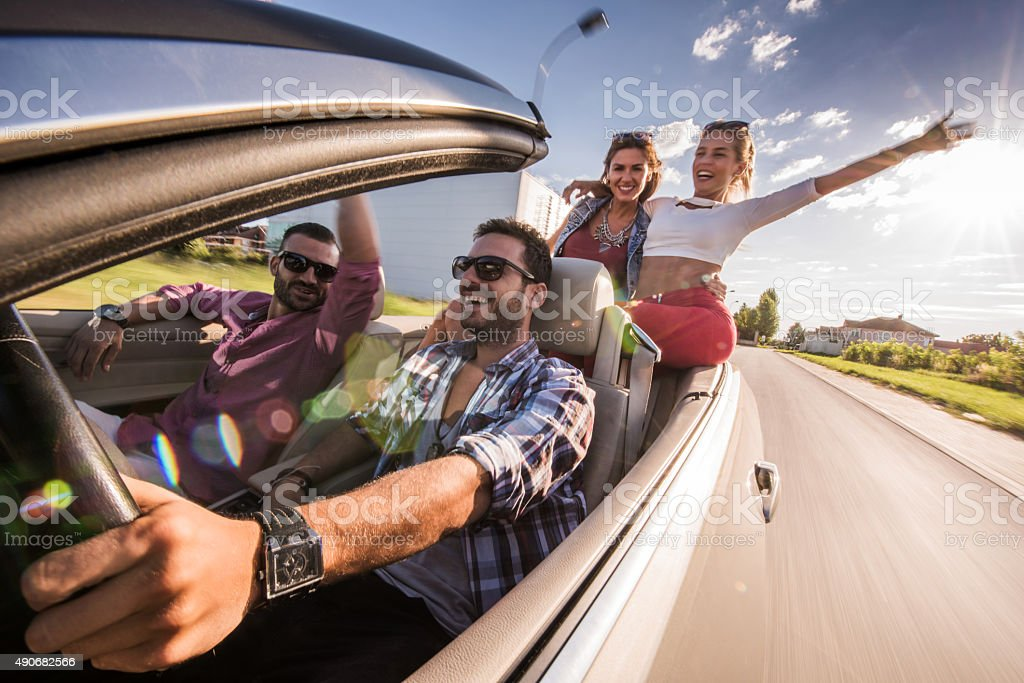 Happy friends having fun while driving convertible car. stock photo