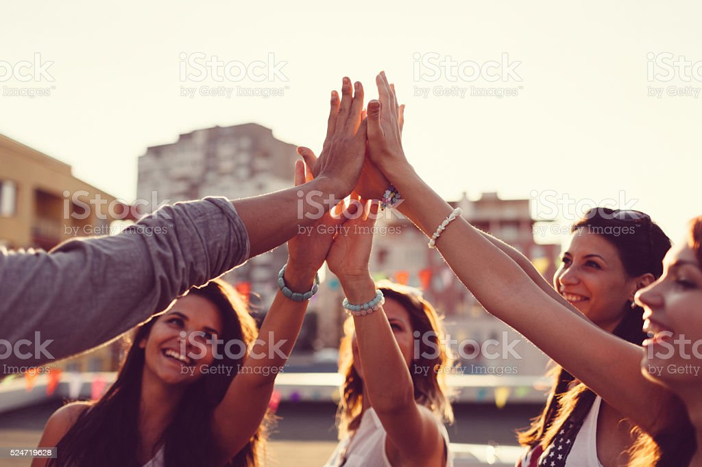 Happy friends high fiving stock photo