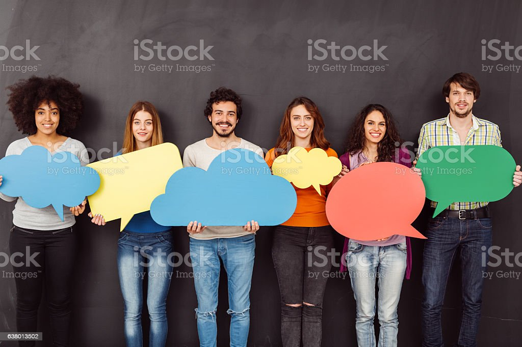 Happy friends holding speech bubbles stock photo