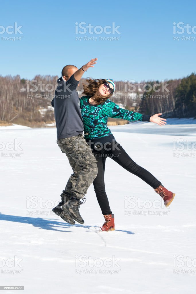 Happy friends jumping on a frozen lake stock photo