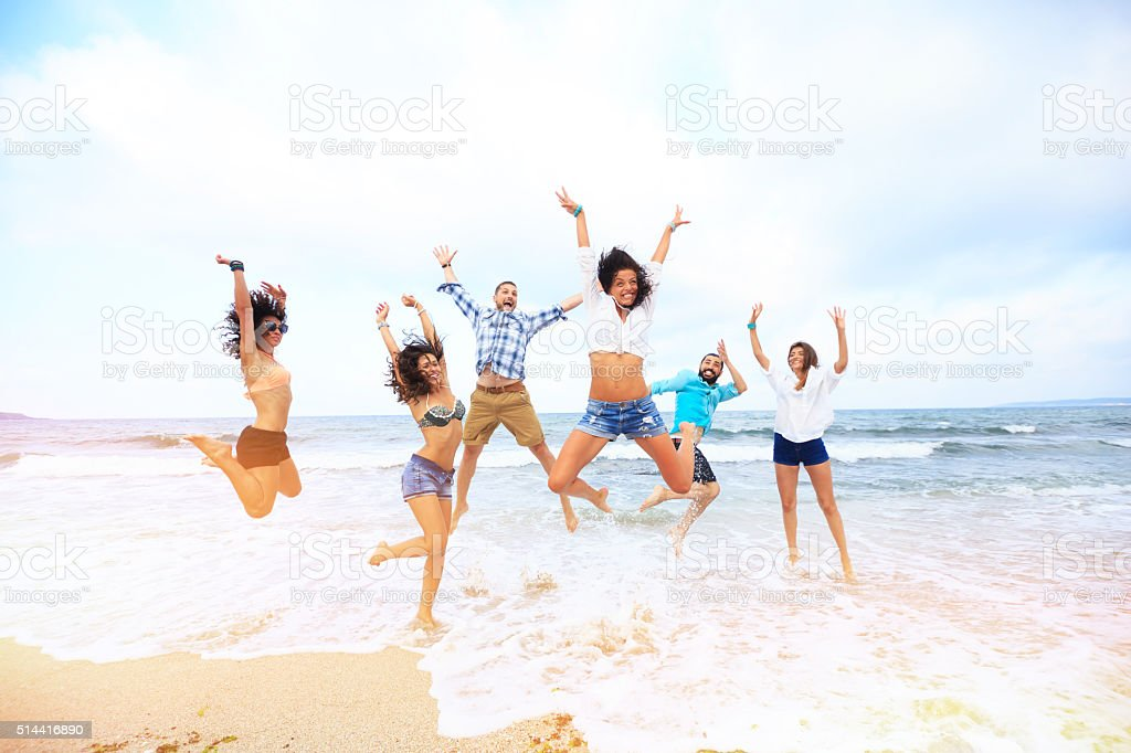 Happy friends jumping over the water stock photo