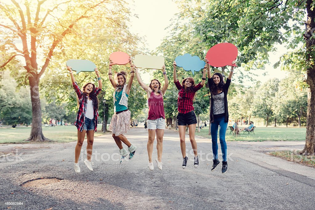 Happy friends jumping with speech bubbles in hands stock photo