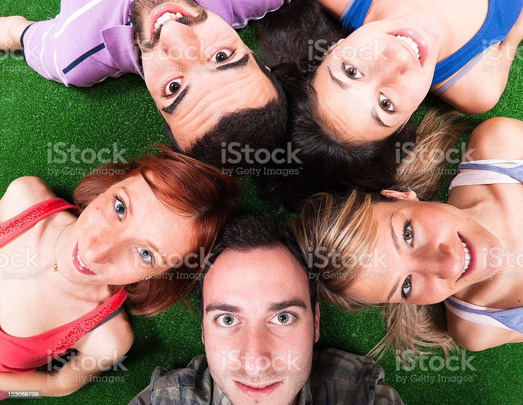 Happy friends Lying on circle in green grass royalty-free stock photo