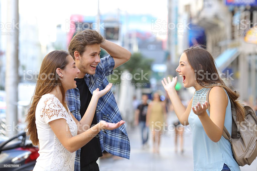 Happy friends meeting in the street stock photo