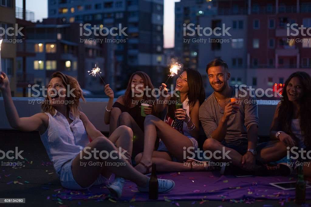 Happy friends on a rooftop party stock photo