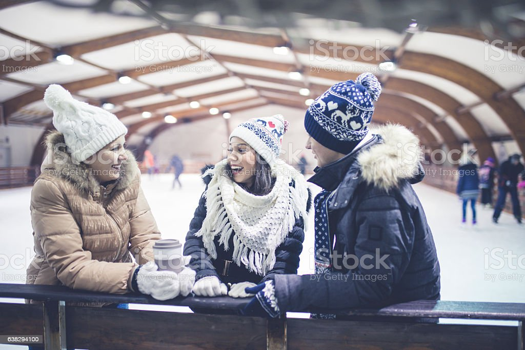 Happy friends on skating rink stock photo