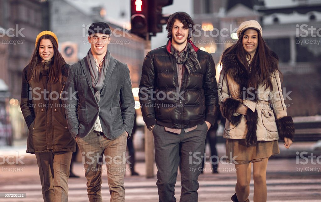 Happy friends on Zebra crossing and looking at camera. stock photo
