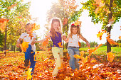 Happy friends play with colorful leaves in forest