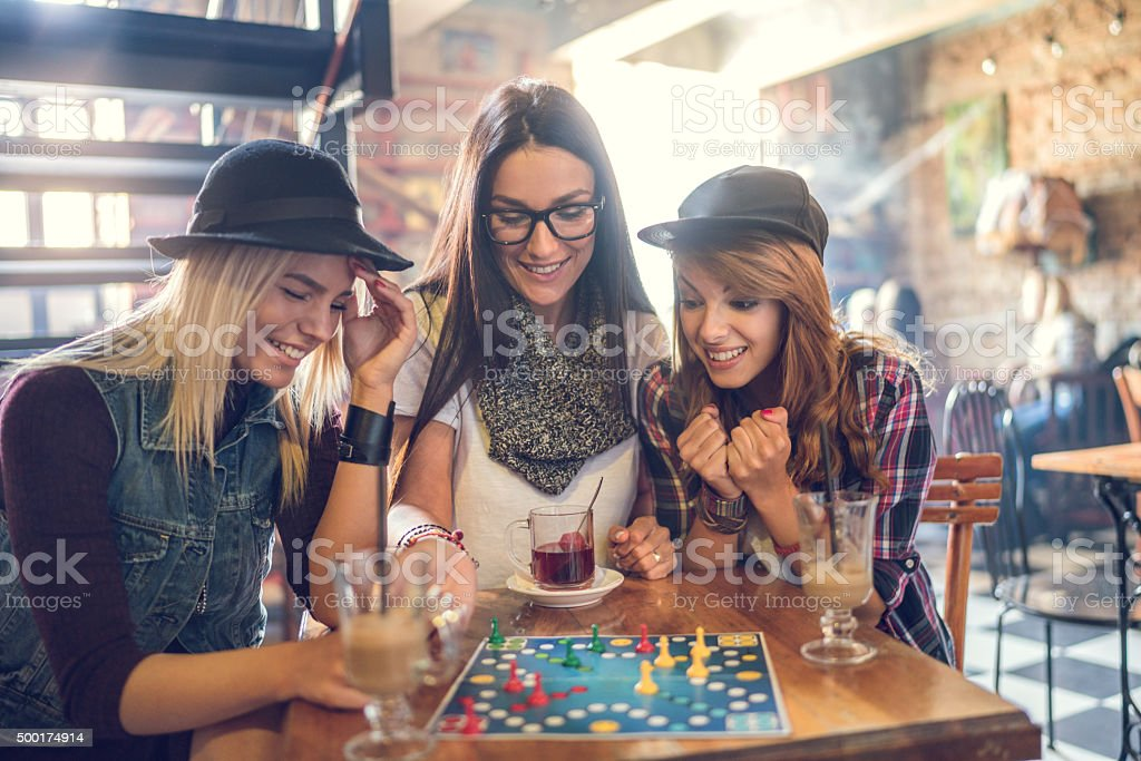 Happy friends playing cross and section game in a cafe. stock photo