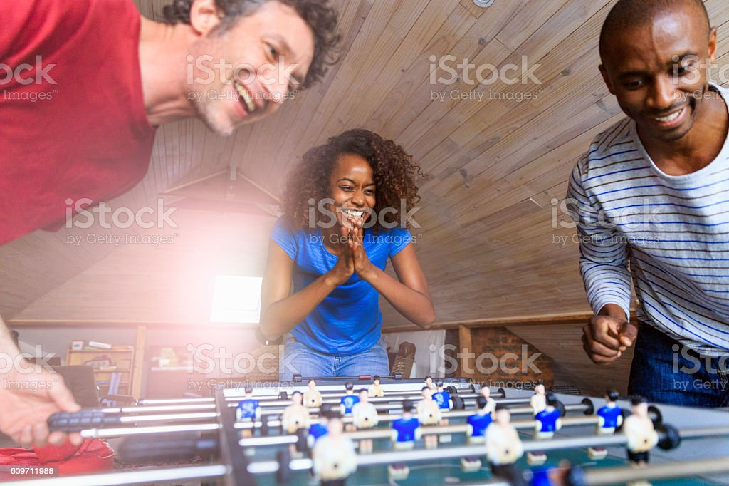 Happy friends playing foosball at home stock photo