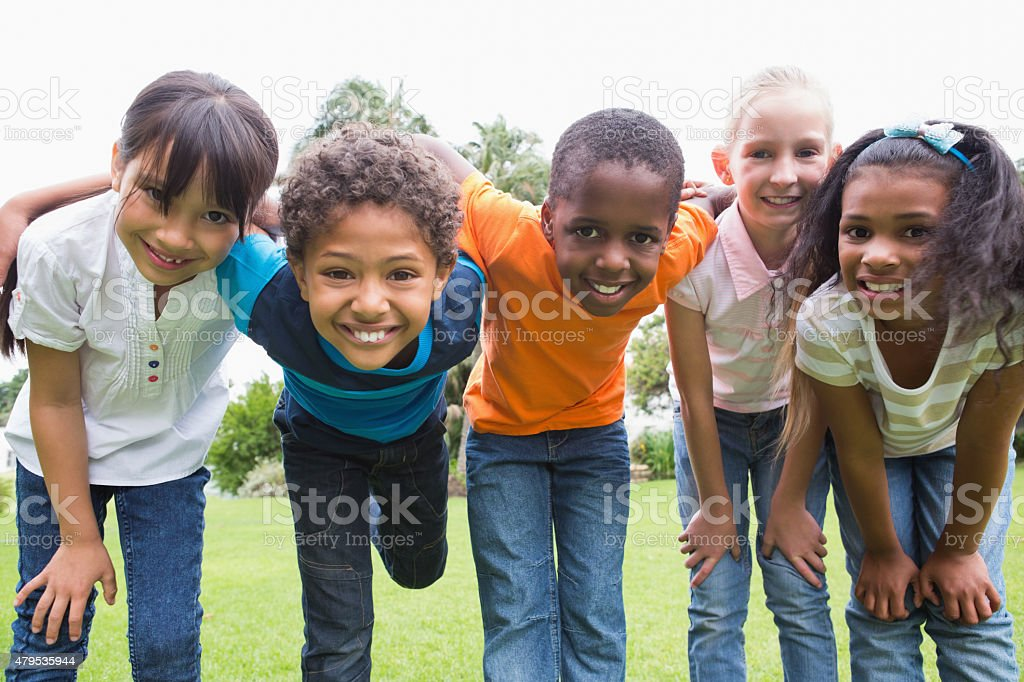 Happy friends playing in the park stock photo