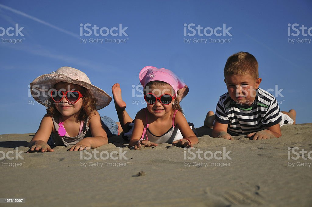 Happy friends playing in the sand stock photo