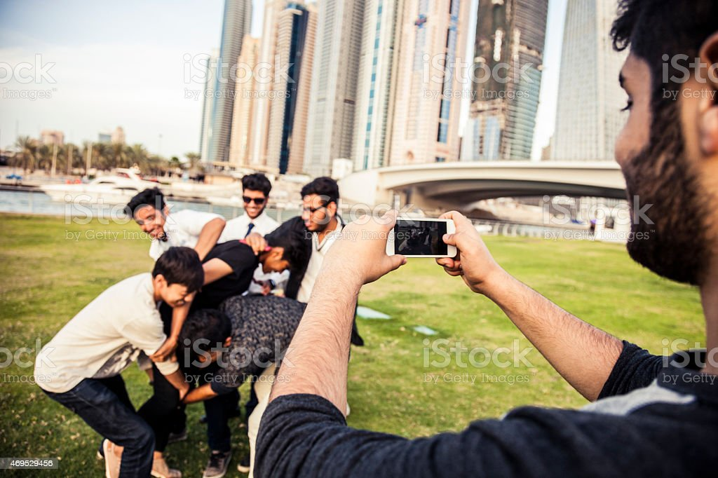 Happy friends playing together in Dubai Marina city park stock photo