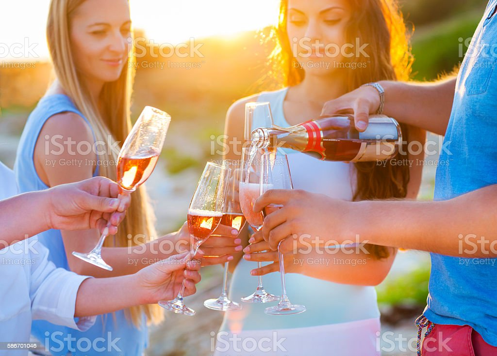 Happy friends pouring champagne sparkling wine into glasses outd stock photo