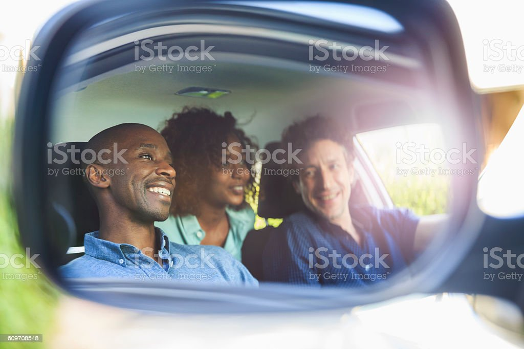 Happy friends reflecting in side-view mirror stock photo