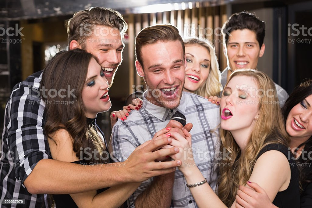 Happy friends singing karaoke together stock photo