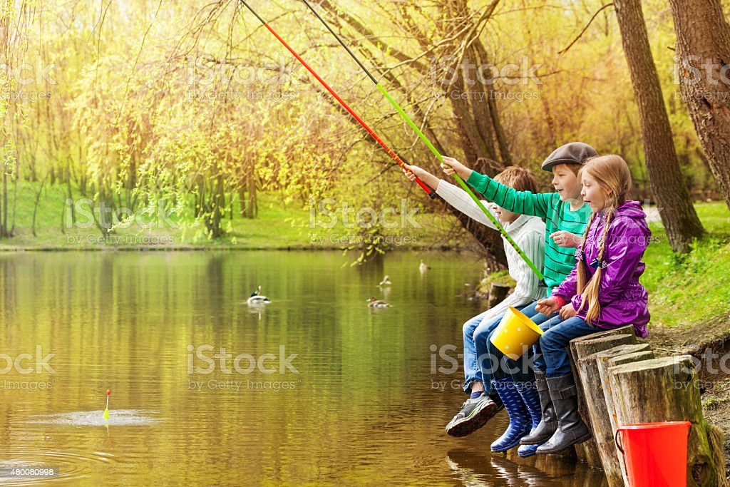 Happy friends sit fishing together near pond stock photo