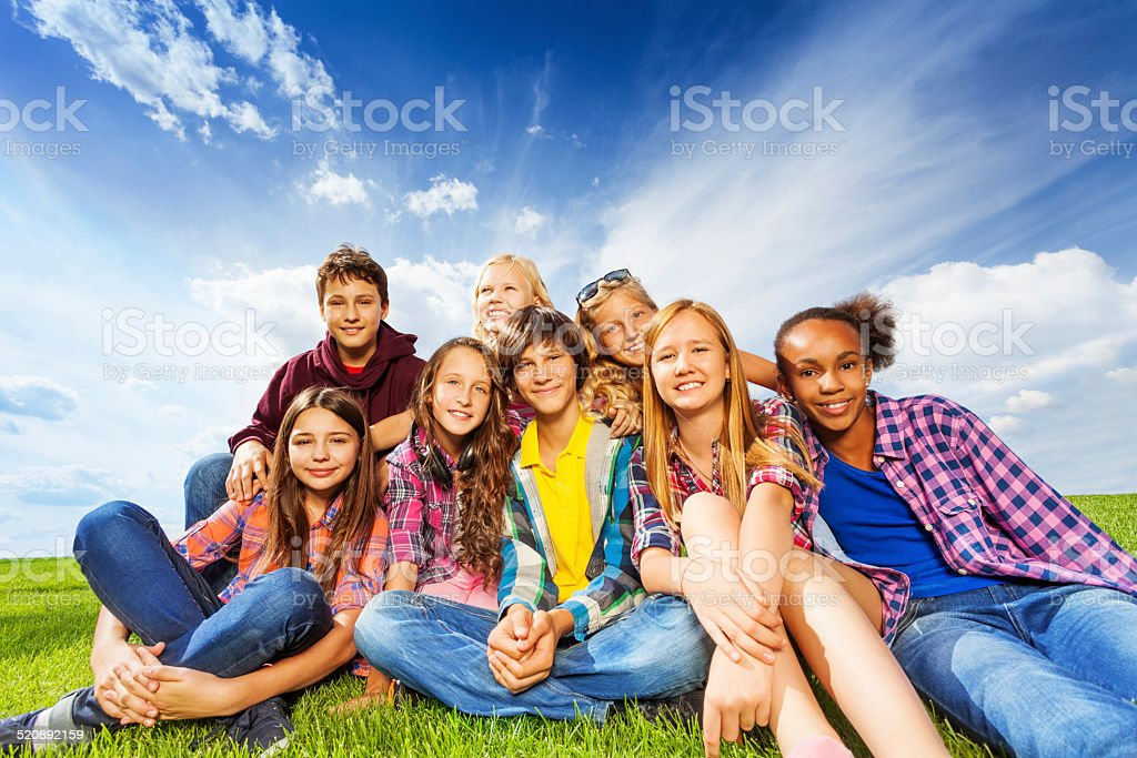 Happy friends sitting on green meadow stock photo