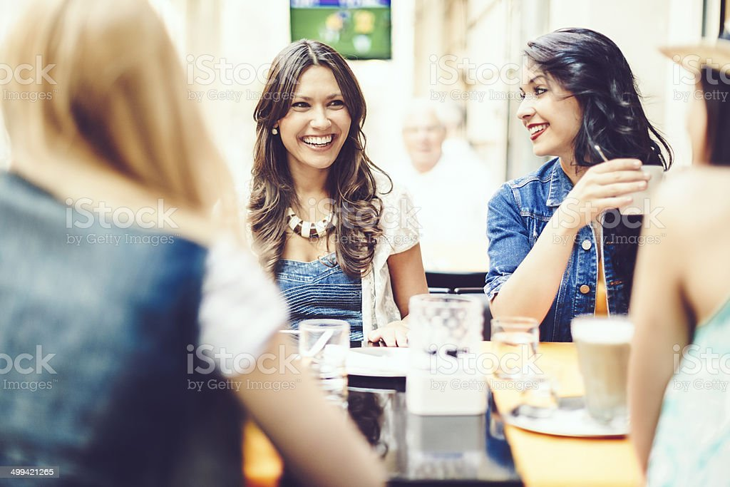Happy friends spending time together in a coffee shop stock photo
