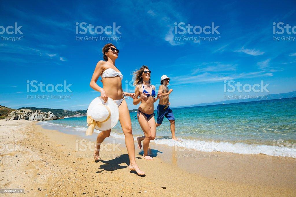 Happy friends splashing shallow water on beach in summer. stock photo