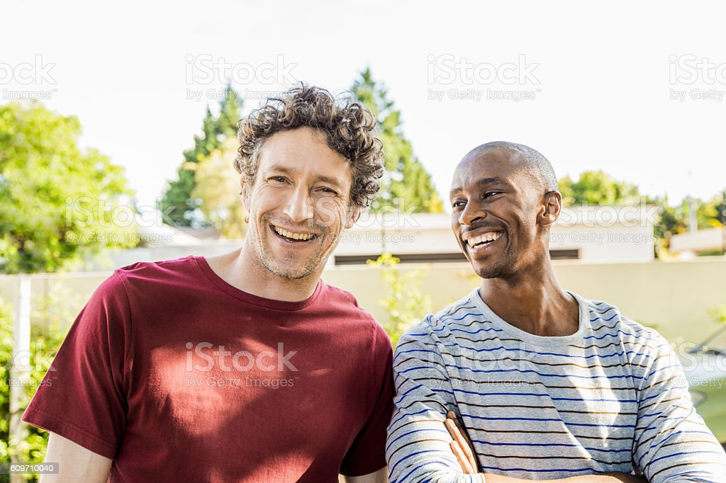 Happy friends standing outdoors against clear sky stock photo