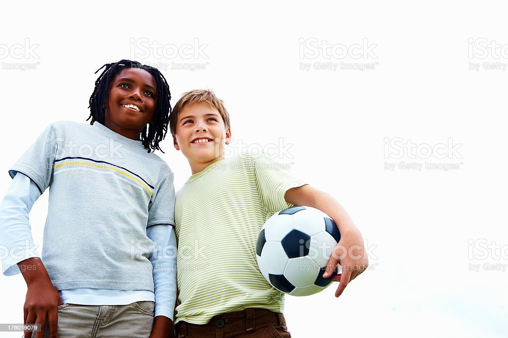 Happy friends standing with a football royalty-free stock photo