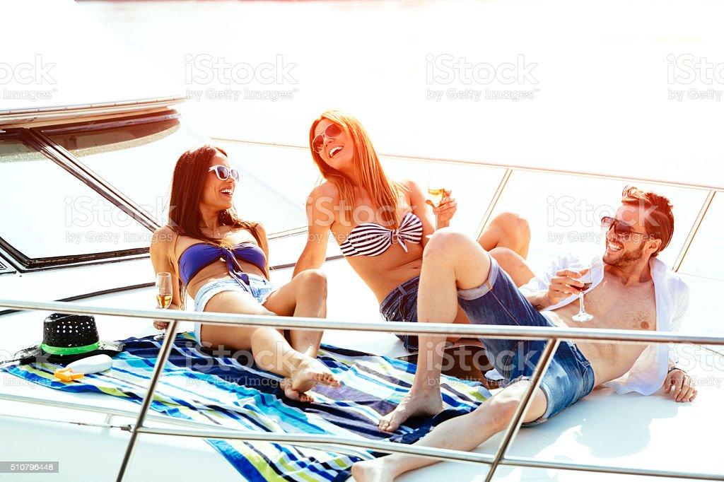 Happy friends sunbathing on yacht. stock photo