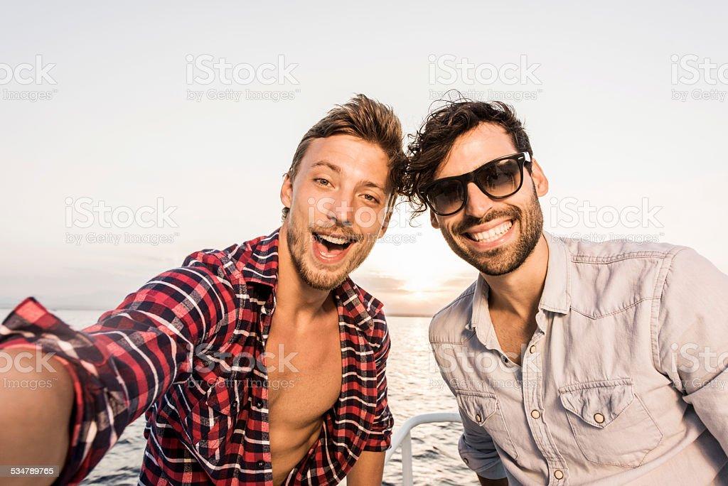Happy friends taking a selfie on boat. stock photo