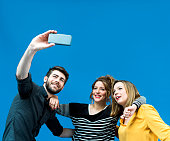 Happy friends taking selfie from mobile phone against blue screen