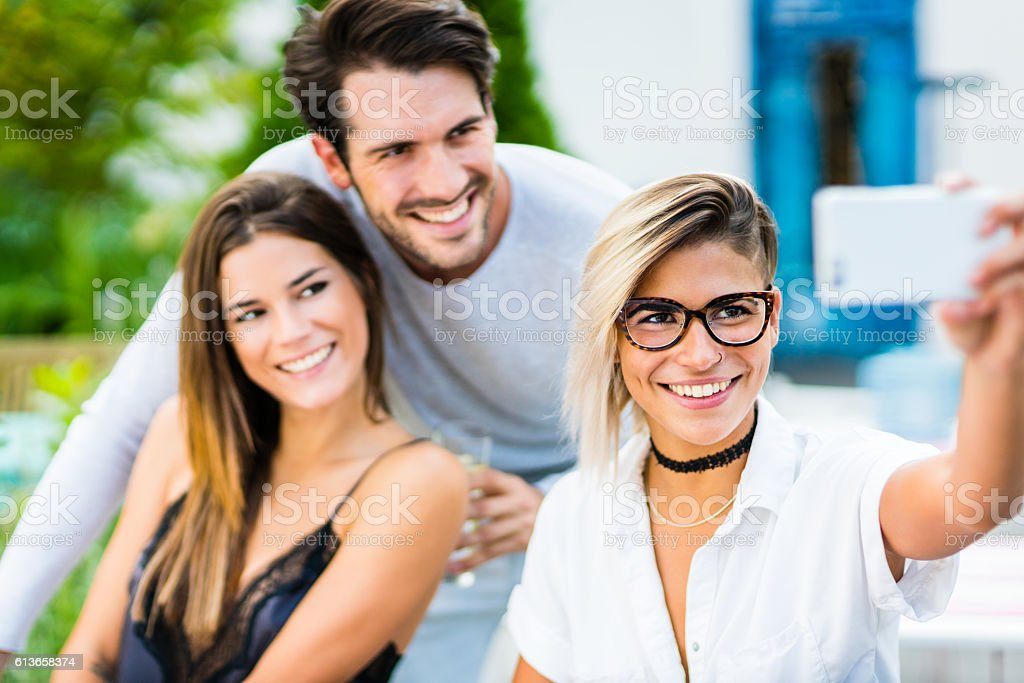 Happy friends taking selfie with smartphone stock photo