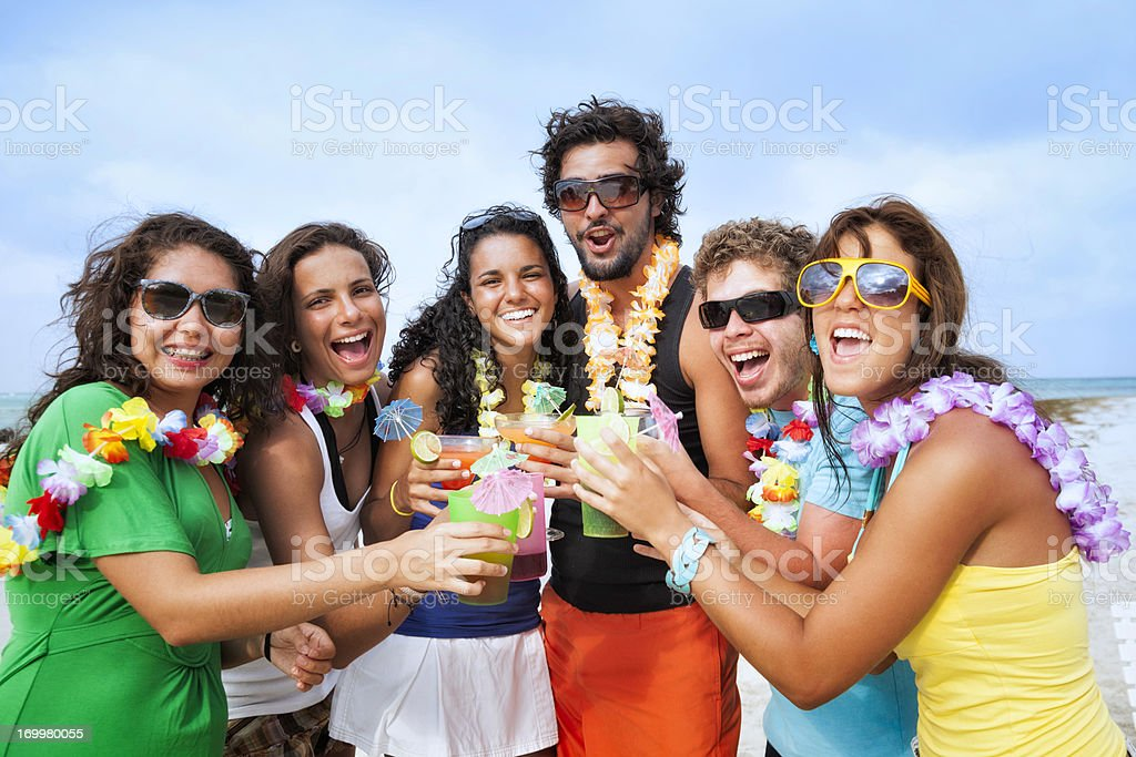 Happy friends toasting during beach party stock photo