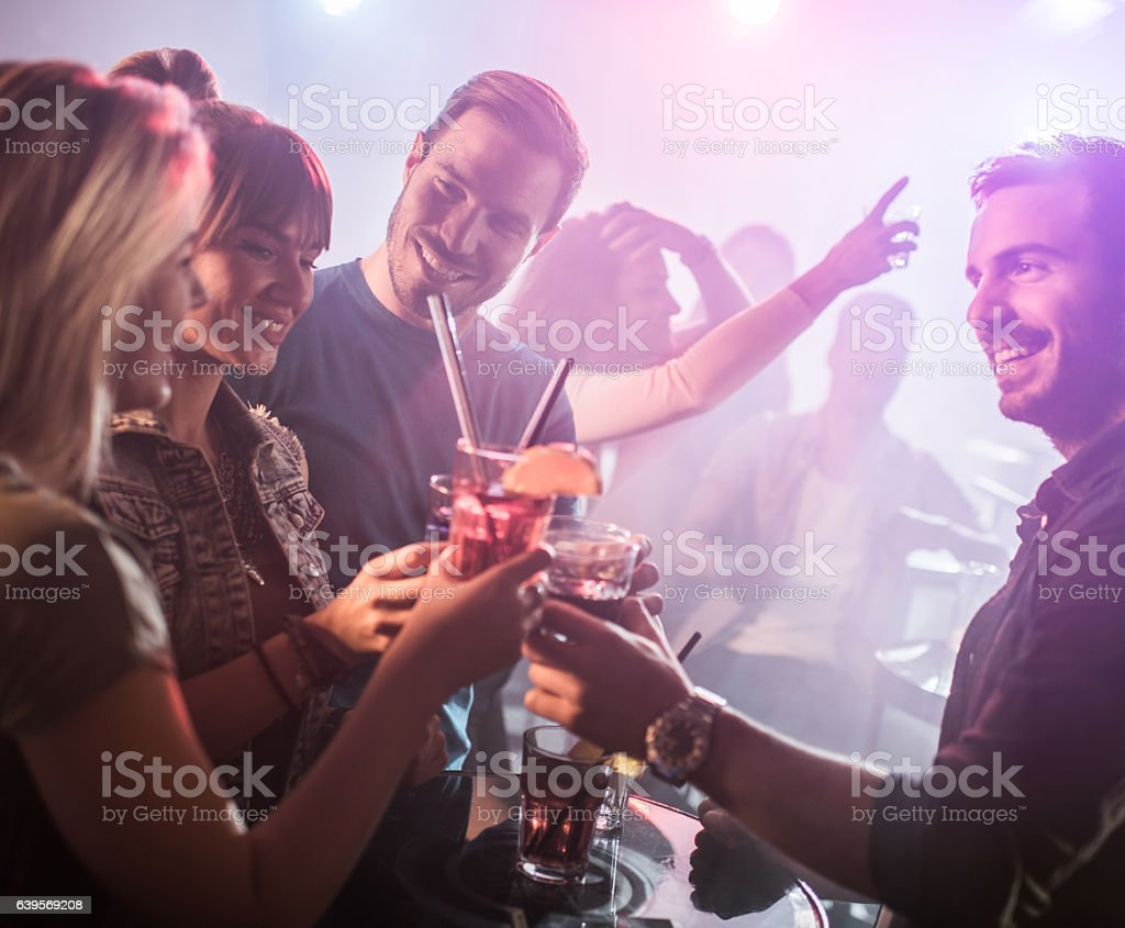 Happy friends toasting while dancing in disco club. stock photo
