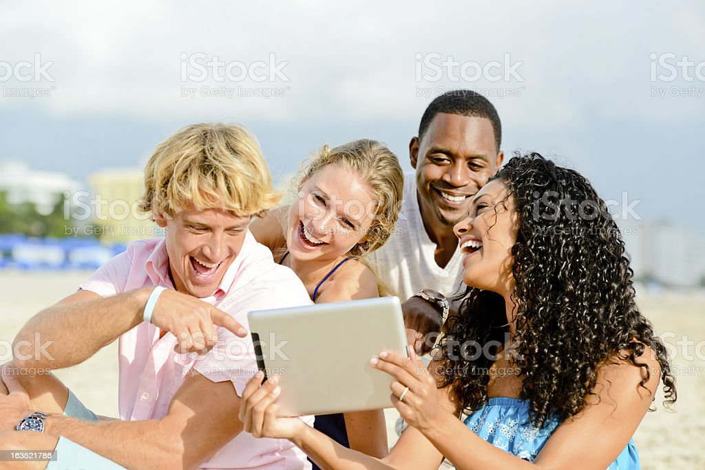 Happy Friends Using Digital Tablet on the Beach royalty-free stock photo