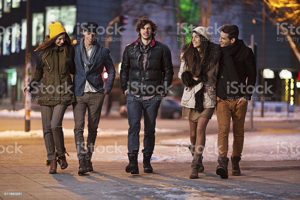 Happy friends walking in the street. stock photo