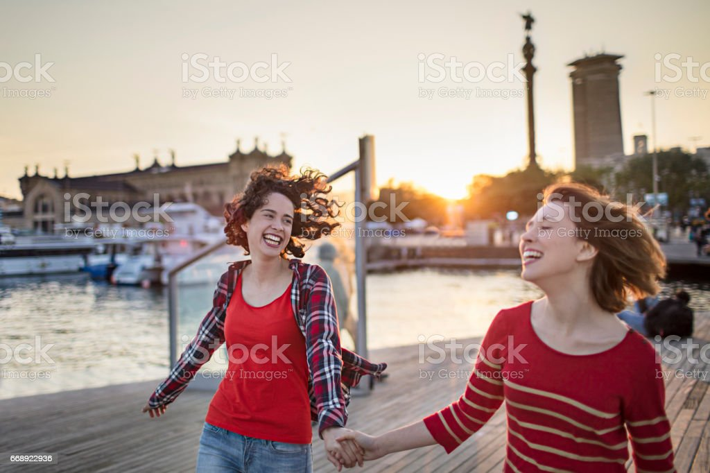 Happy friends walking while holding hands at port stock photo