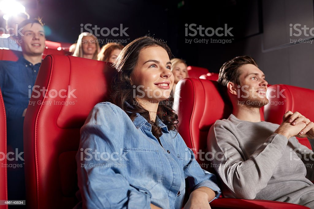 happy friends watching movie in theater stock photo