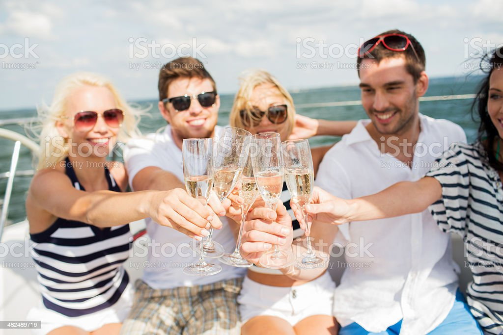 happy friends with glasses of champagne on yacht stock photo