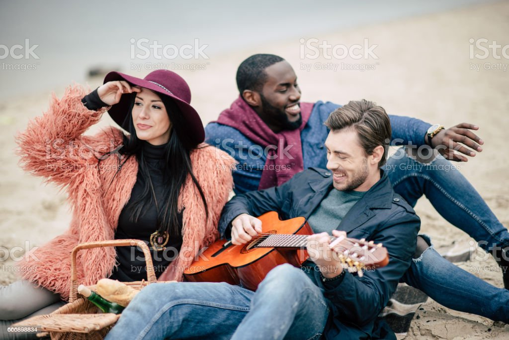 Happy friends with guitar at picnic stock photo