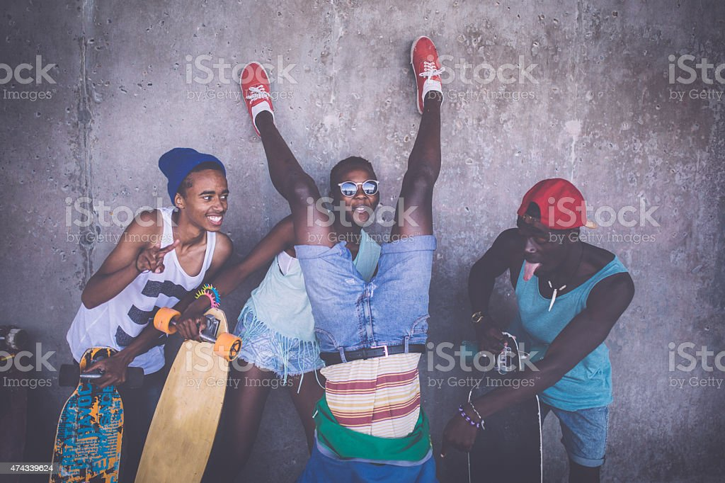 Happy friends with longboards having fun with crazy poses stock photo