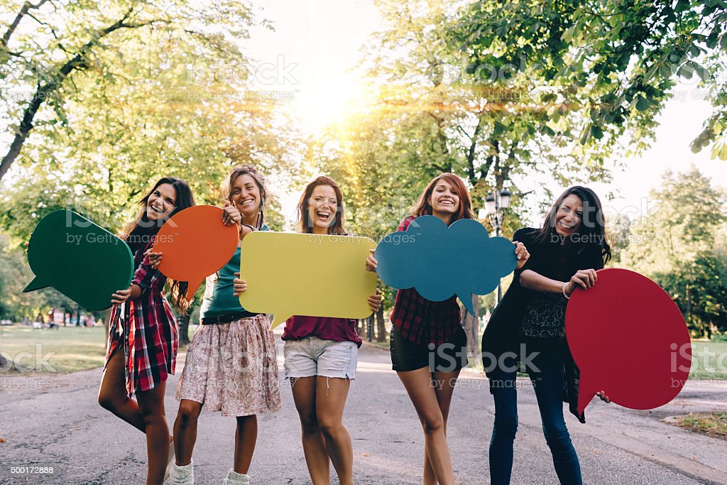Happy friends with speech bubbles smiling to the camera stock photo