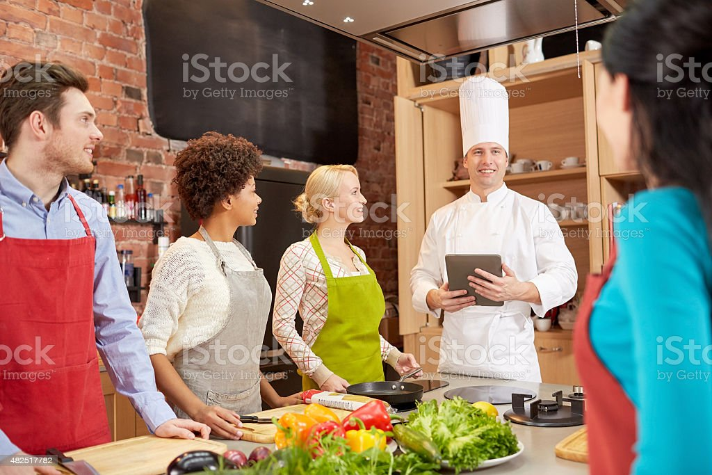 happy friends with tablet pc in kitchen stock photo