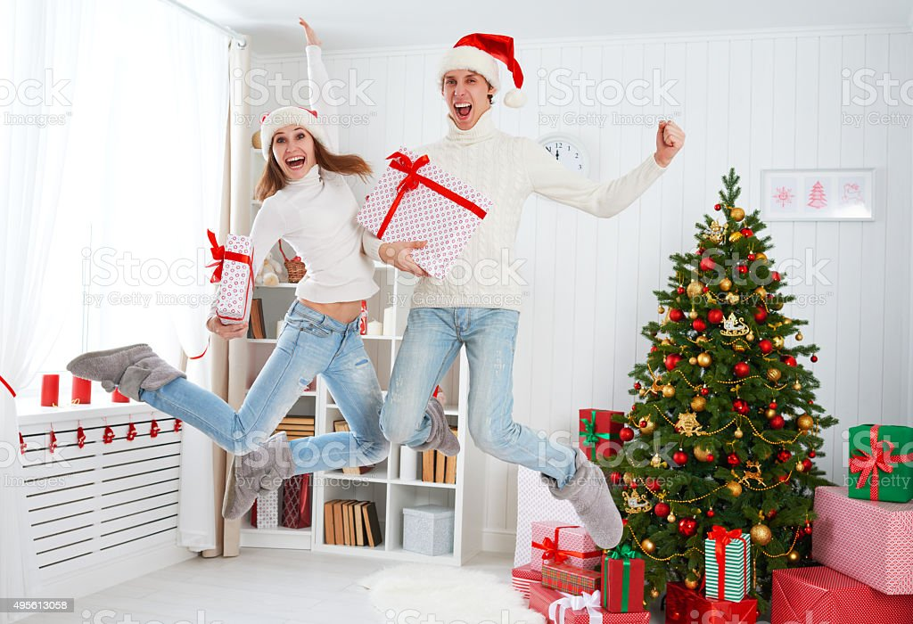 Happy funny family couple jumping and having fun on Christmas stock photo