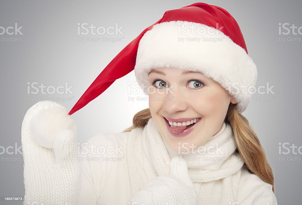 happy funny girl in a Christmas hat on gray background royalty-free stock photo