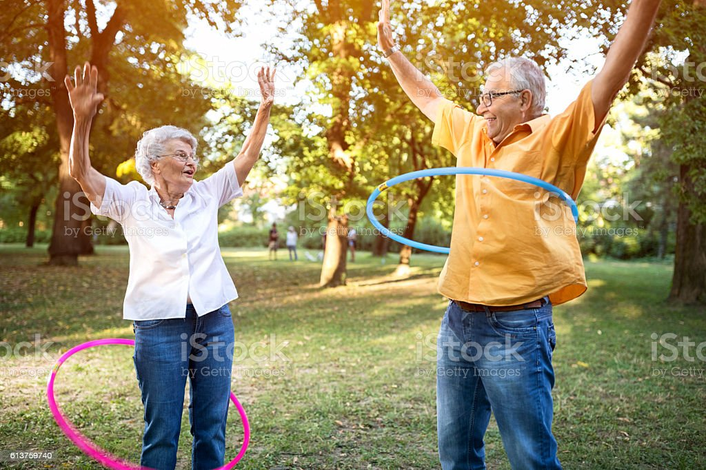 Happy funny senior couple playing hulahop in park stock photo
