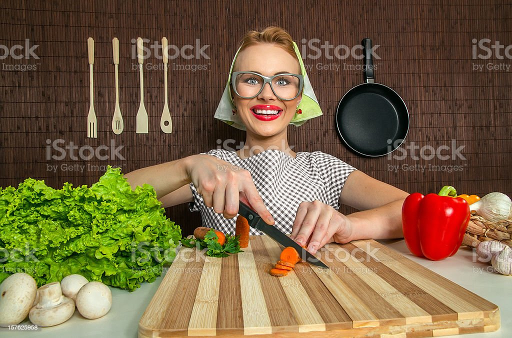 Happy funny woman cook working in the kitchen cutting carrot stock photo