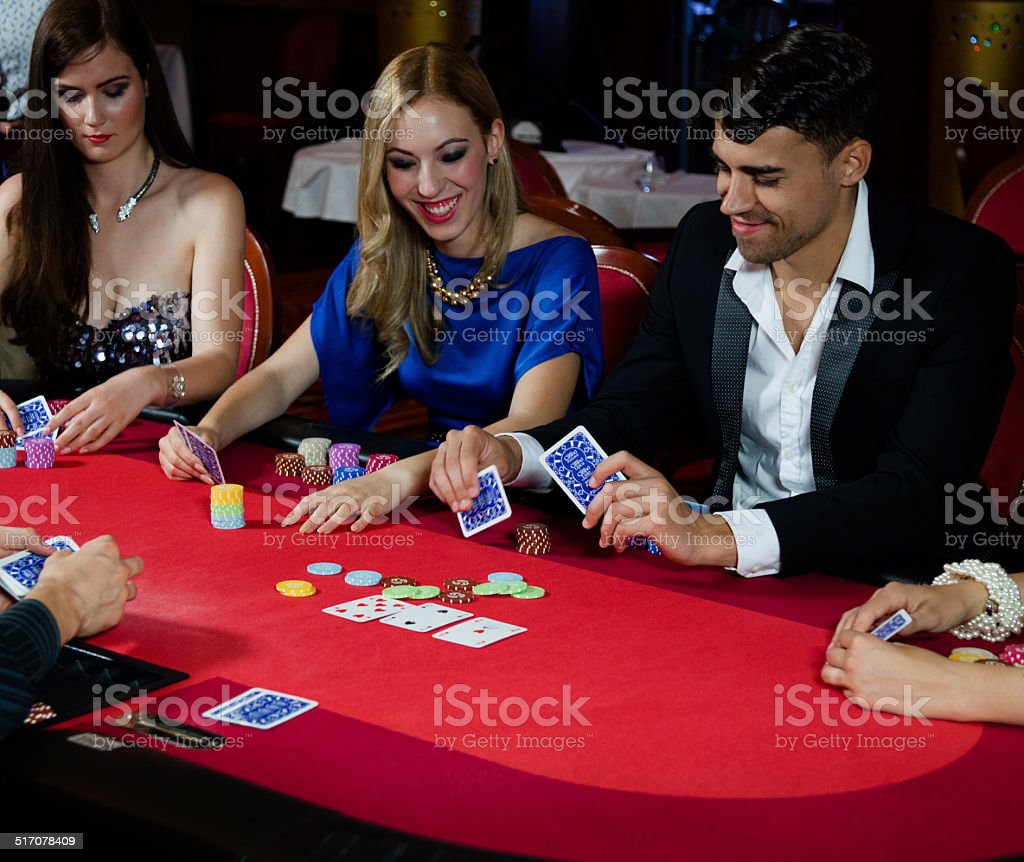 happy gamblers have fun playing poker in casino stock photo